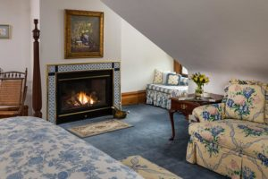 A view inside a luxury room with a roaring fireplace