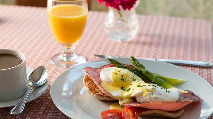 A breakfast of orange juice, eggs, ham and toast