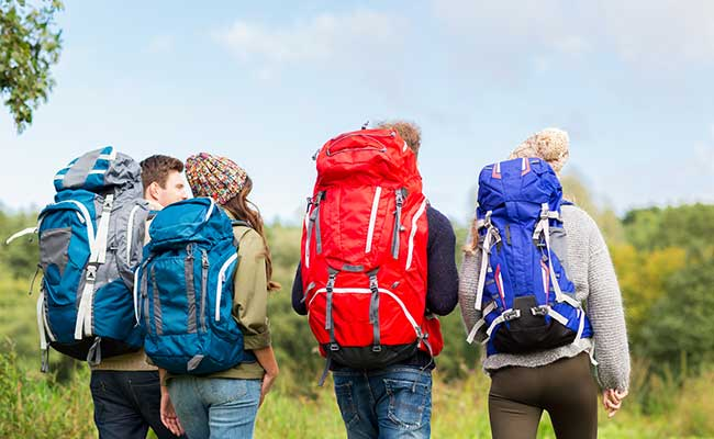A group of backpackers walking through a field