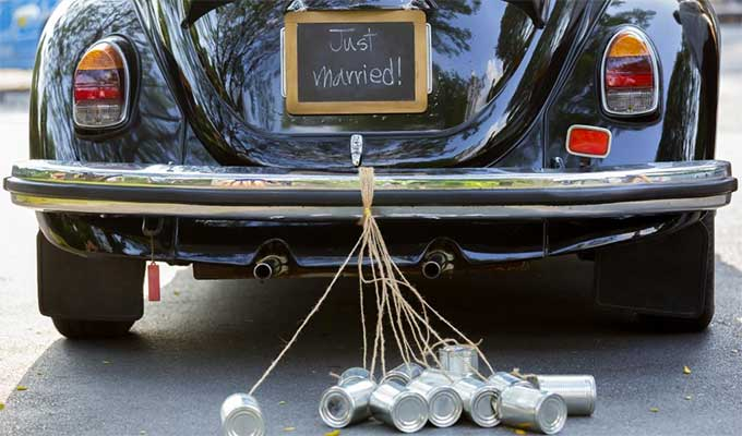 A black Volkswagen Beetle pulling cans and displaying a 'Just Married' sign