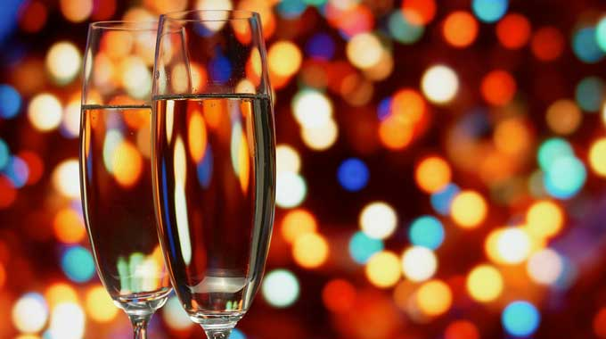 Two glasses of champagne in front of glowing colored lights