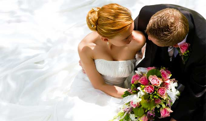 Newlyweds embrace while the bride holds a colorful bouquet