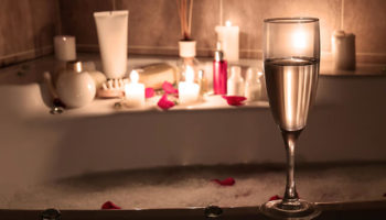 Wine glass, candles, and bath items in the bath tub