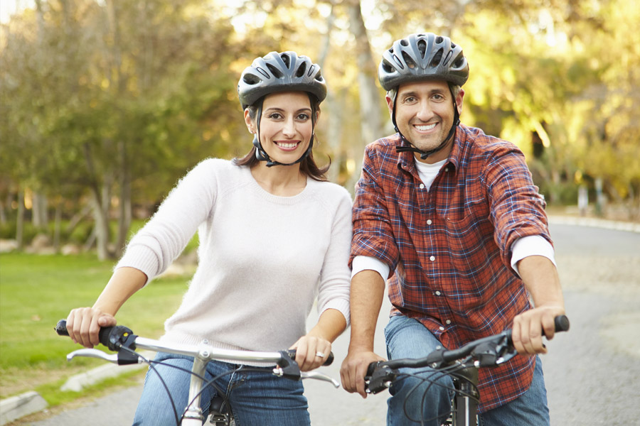 Middle aged woman and man sitting on bikes with helmets, with trees and road behind them.