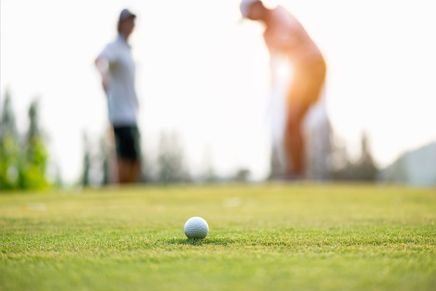 two fuzzed out golfers with a golf ball clear in the front promoting Discounted Golf at Whitetail