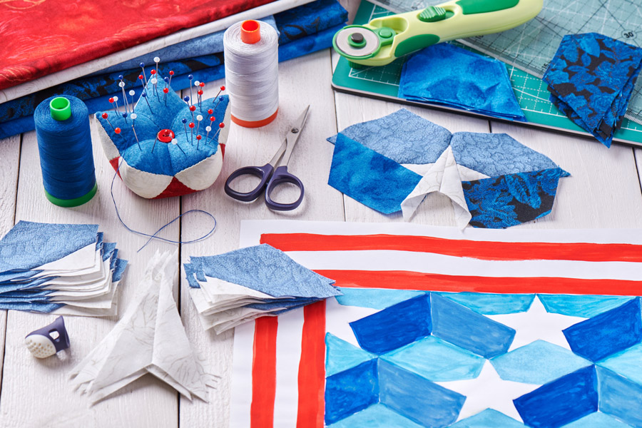 sewing materials and cut pieces of fabric to make a quilt with an American theme