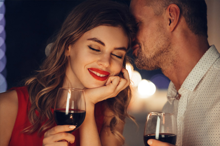 Woman with red lipstick holding glass of wine, leaning into a man whispering into her ear holeing a glass of win