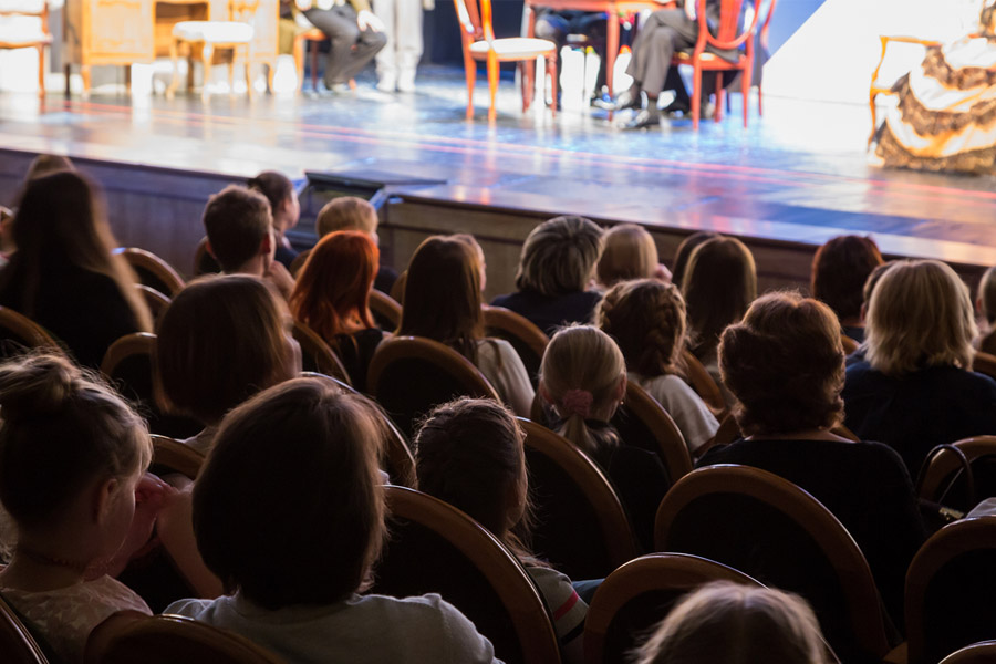 Back of the head view of an audience watching a generic play on stage