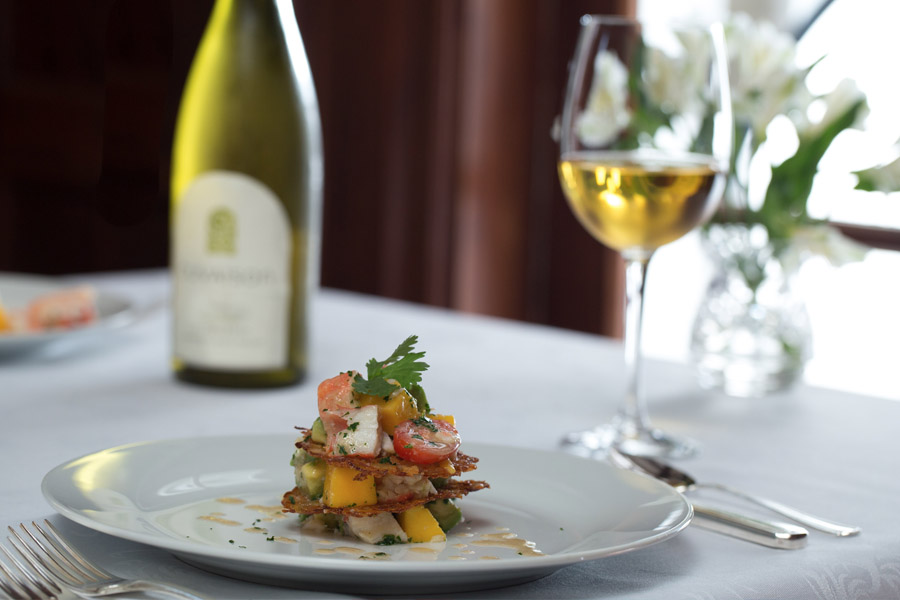 bottle of fuzzed out wine in the background on a white table cloth, with a glass of wine and place of stacked ahi and mango