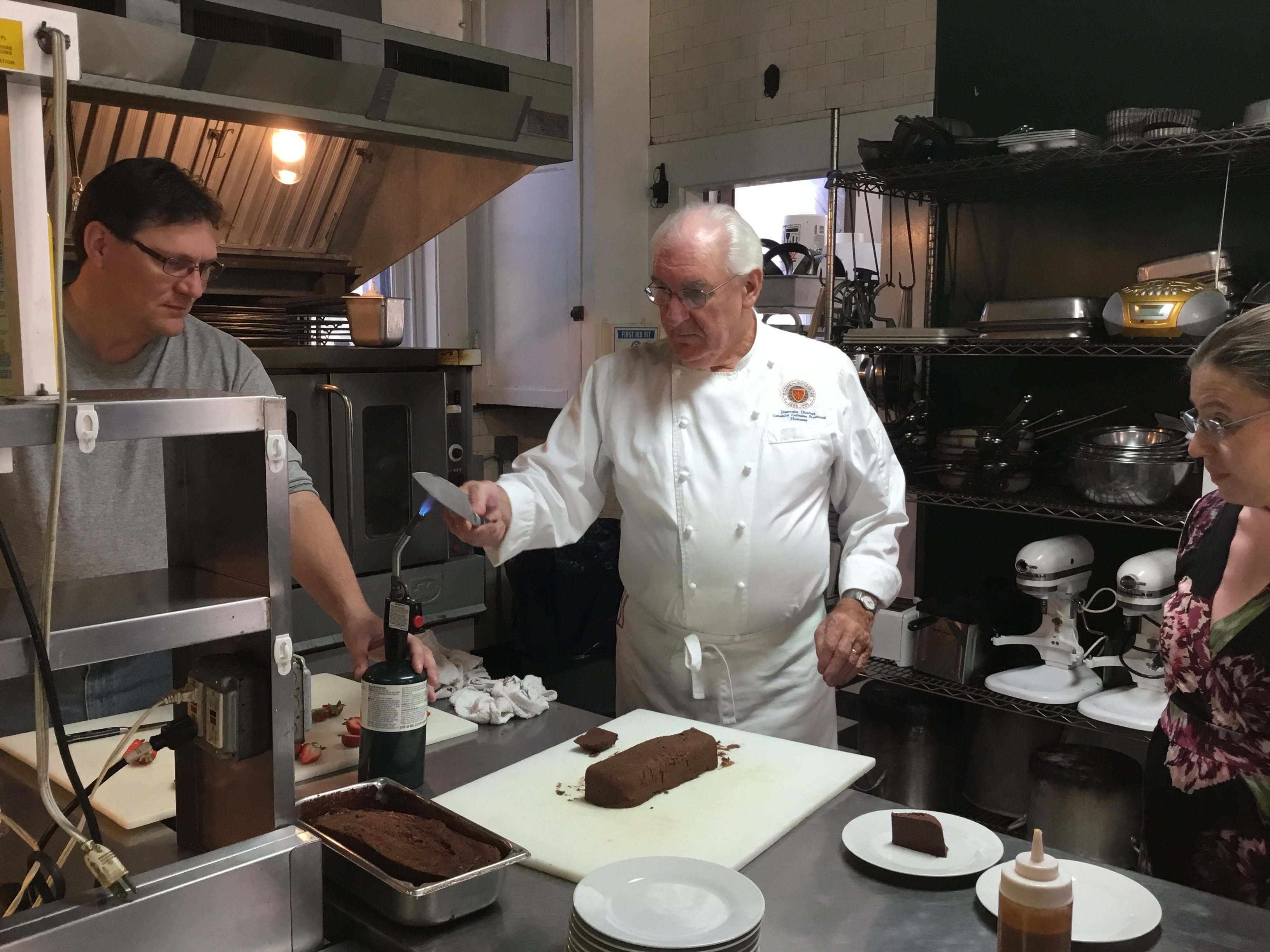 The Chef in French Cooking Class is cutting the dessert