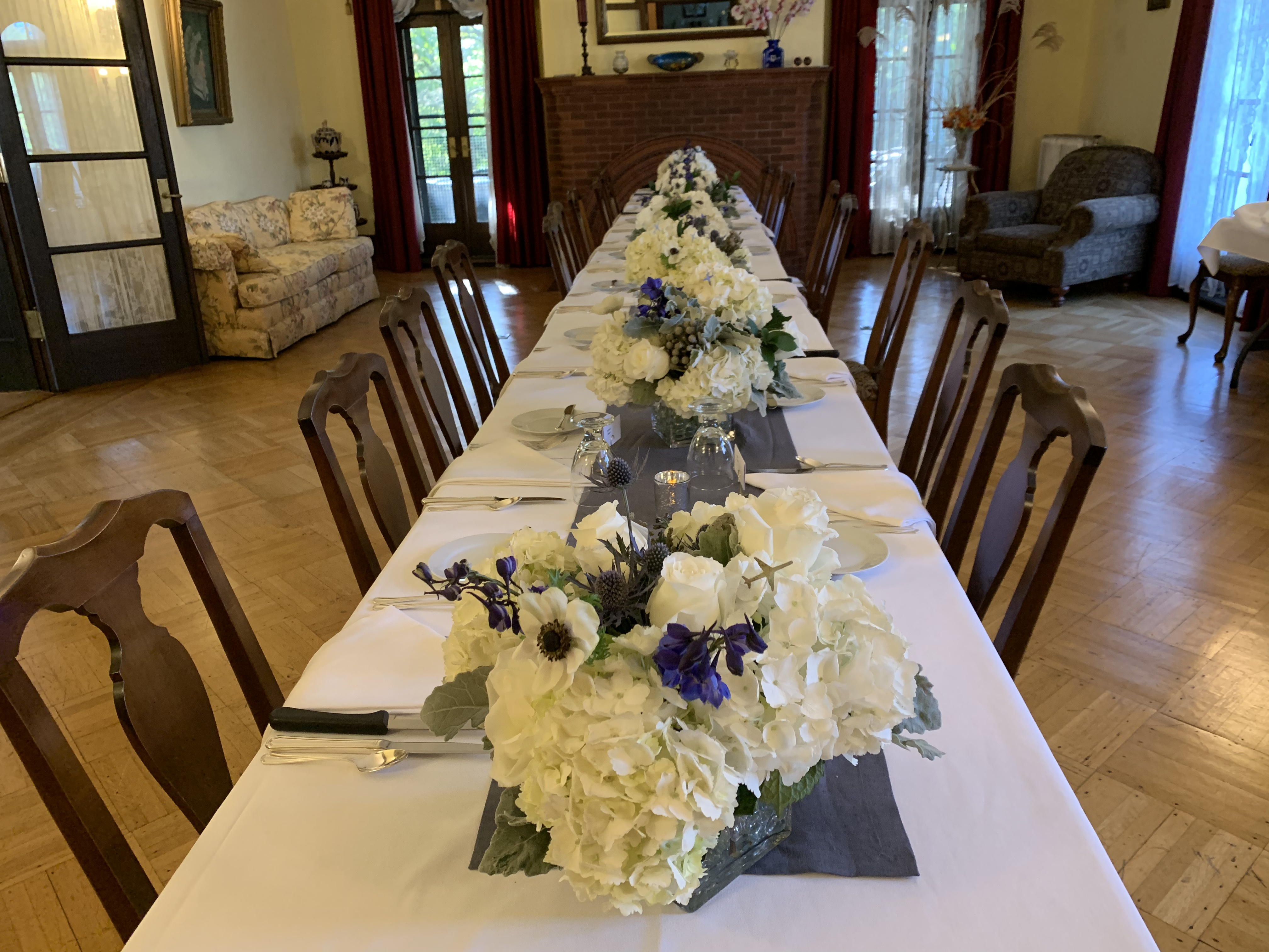 Table set-up with flowers, plates, and silverware for a wedding rehearsal