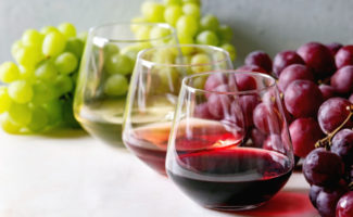 Variety of wines in stemless wine glasses with grapes in the background