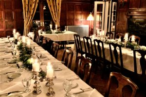 Dining tables with plates, glasses, silverware, candles and leaves at Byron's Dining