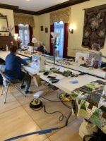 Quilting Weekend: students are quilting in a big roomrees
