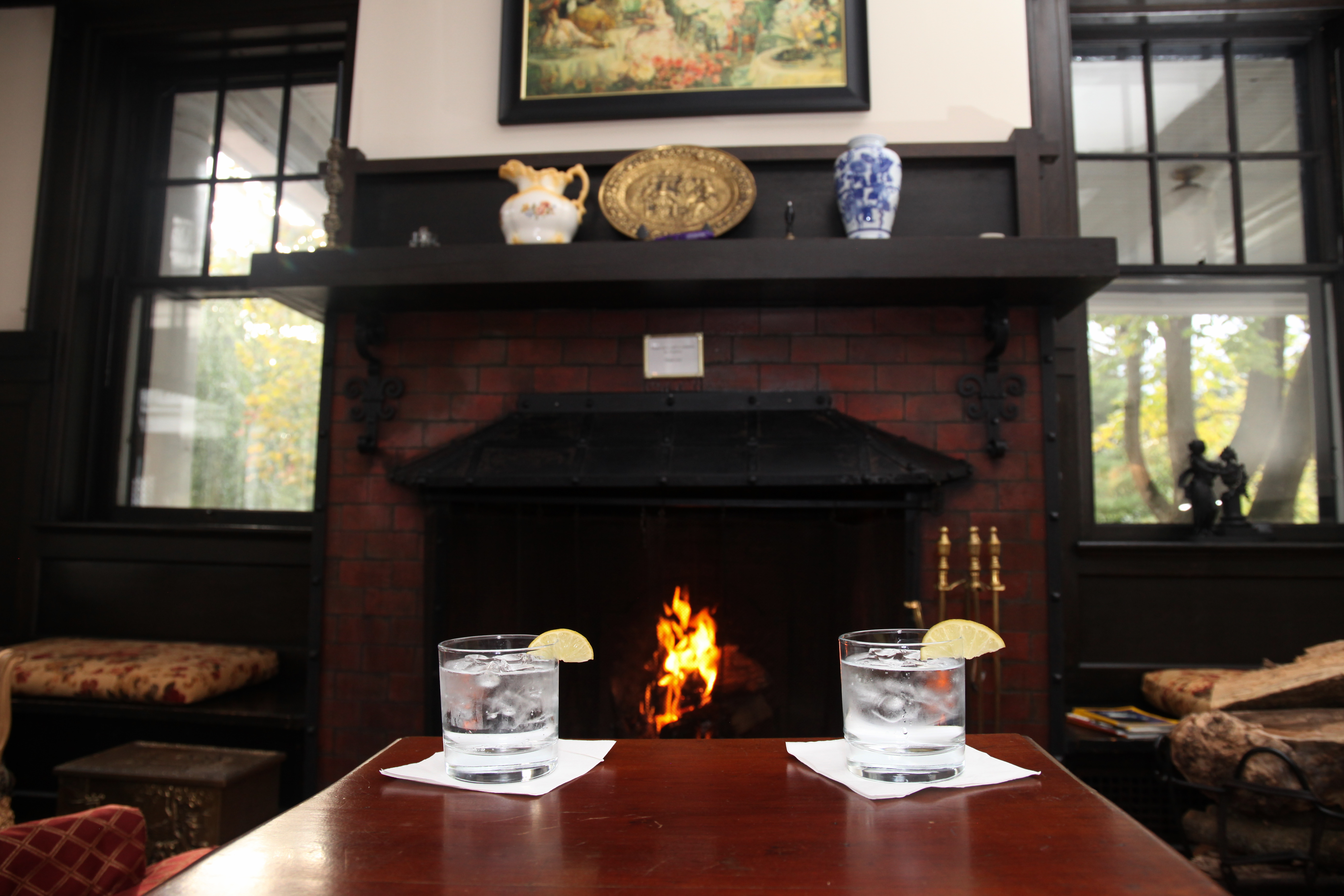 Two glasses of liquor on a table in front of the fireplace at the bar