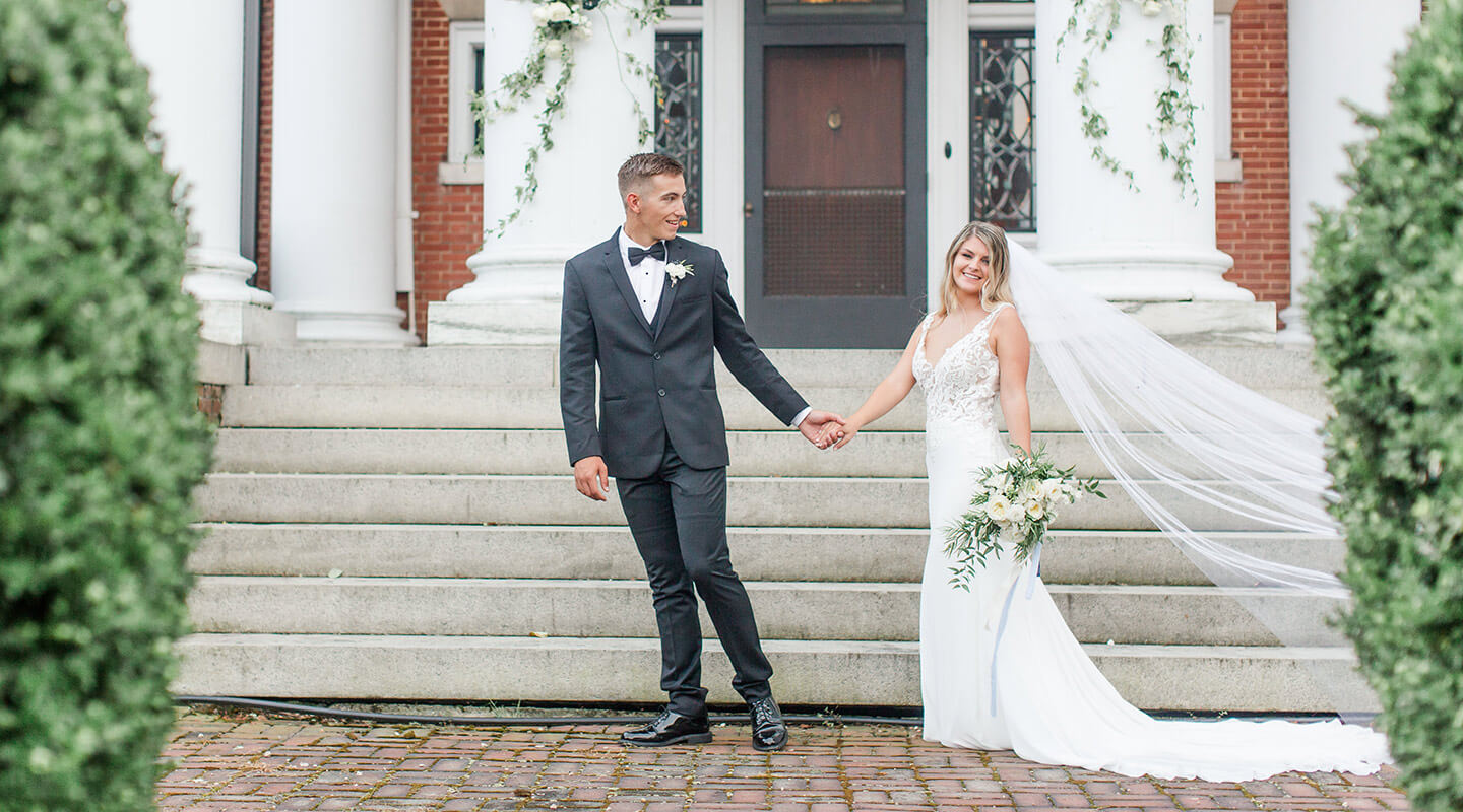 Bride and groom holding hands on the front steps