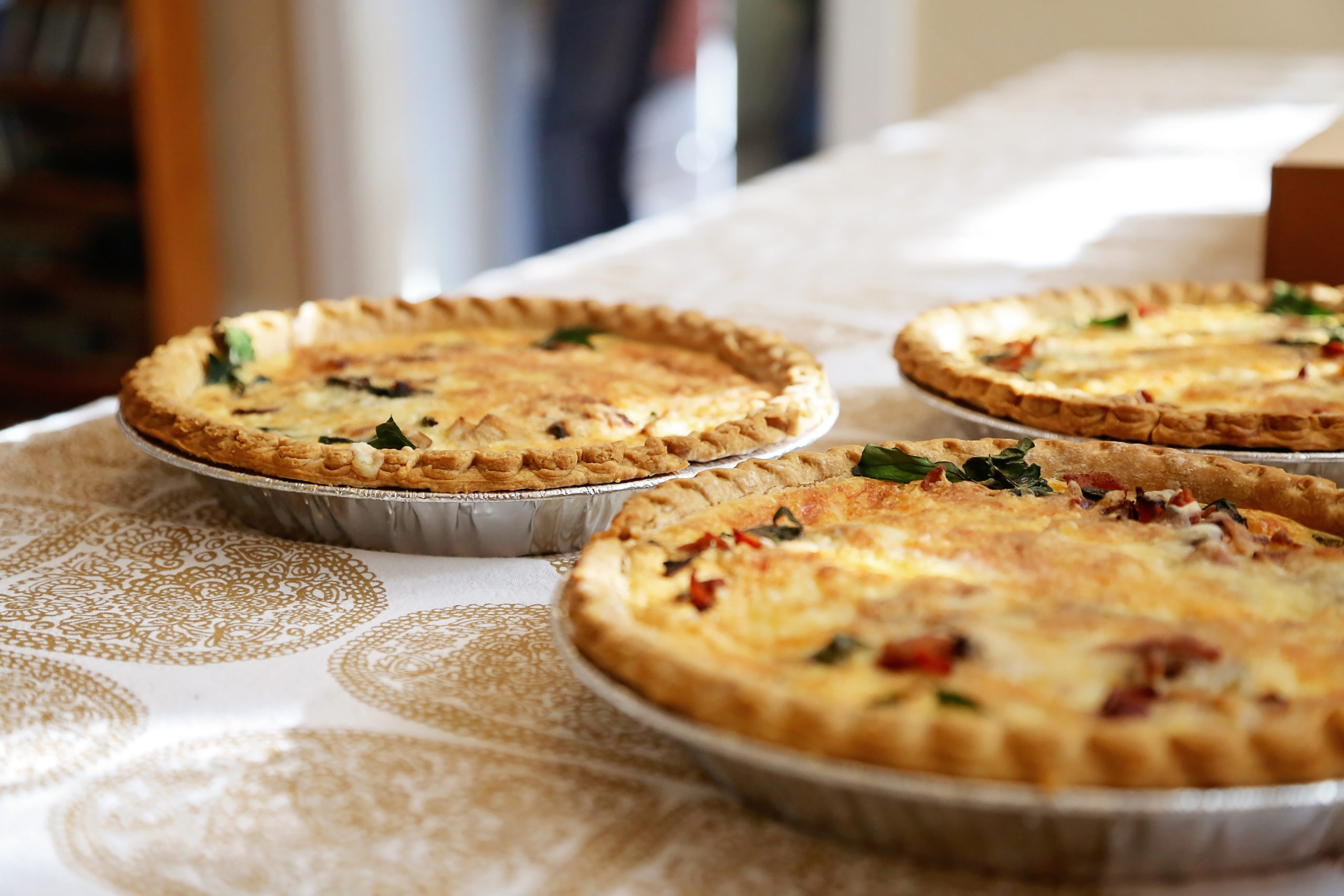 three spinach quiches on a table