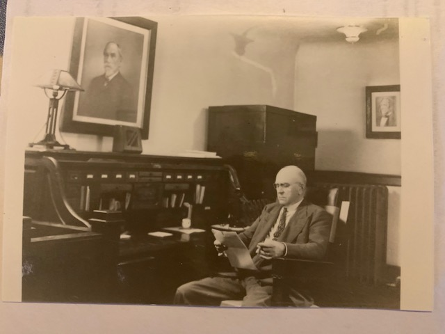 Harry Byron is sitting at his desk and reading newspaper.