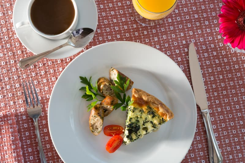 A breakfast quiche served with sausage, coffee, and orange juice
