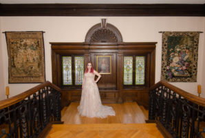 Bride standing in front of the portrait of the lady of the house standing on the staircase