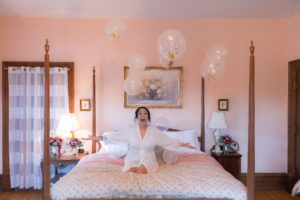 A bride and balloons on the bed