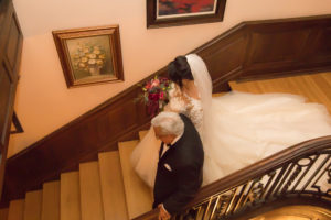 The bride and her father walking on the stairs