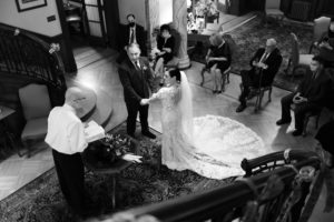 A wedding held at the lobby. There are the officiant, guests and a wedding couple.