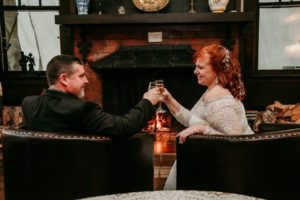 A wedding couple having the first toast in front of a fireplace