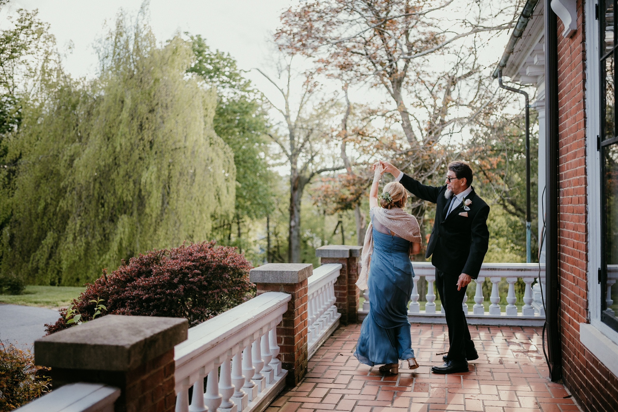 A wedding couple is dancing on the porch